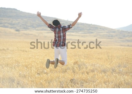 Young man jumping on yellow meadow - stock photo