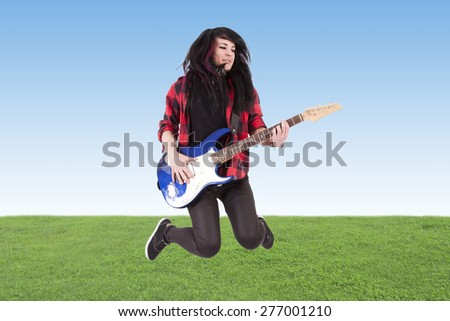 young man jumping with electric guitar - stock photo