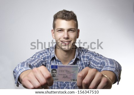 Young man just received his drivers license and is happy to drive his own car soon - stock photo