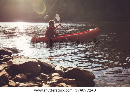 Young man kayaking in a lake. Young guy paddles his kayak on a sunny day. - stock photo