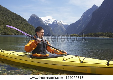 Young man kayaking in peaceful lake with mountains in background - stock photo