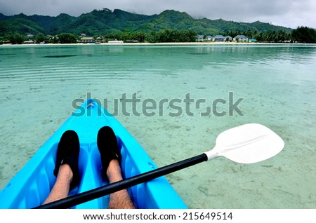Young man kayaking in sea at over turquoise water during travel vacation in a tropical Island.Rarotonga Cook Islands. Concept photo of women freedom, travel, vacation. Copyspace - stock photo