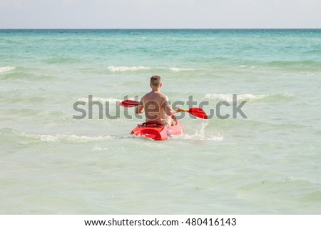 Young man kayaking in the sea