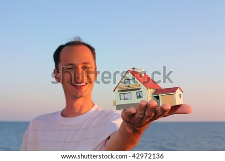 Young man keeps in hand model of house with garage - stock photo