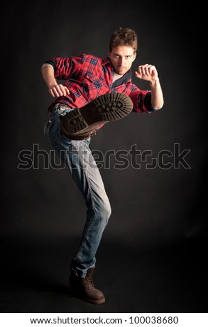Young man kick against black background. - stock photo