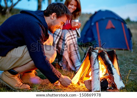 Young man kindling firewood in the countryside with girl and tent on background - stock photo