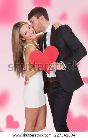 Young man kissing girlfriend while holding paper heart over colored background - stock photo