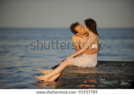 Young man kissing his girlfriend on a pier