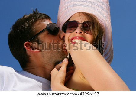 Young man kissing his girlfriend on the cheek - stock photo