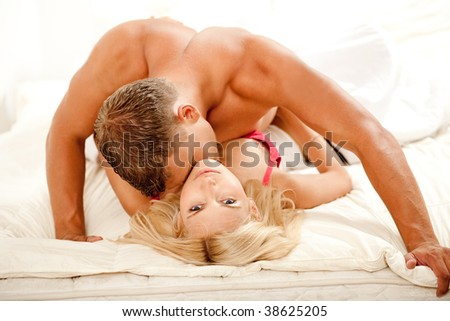 Young man kissing his wife as she looks into camera - stock photo