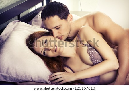 Young man kissing woman in darkness bedroom on bed - stock photo