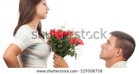Young man kneeling and giving bouquet of roses to his girlfriend isolated on white backgrpund.