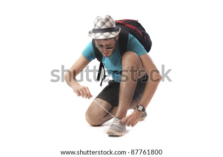 Young man lacing up his shoes - stock photo