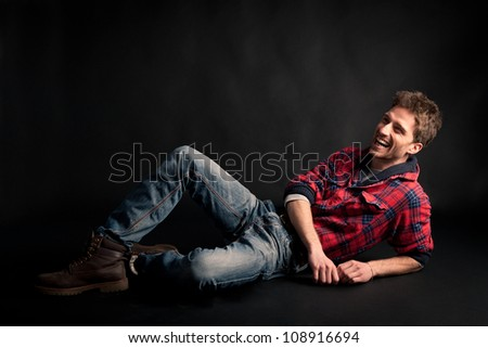 Young man laughing against black background.