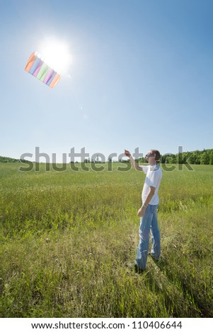 young man launch kite in field - stock photo