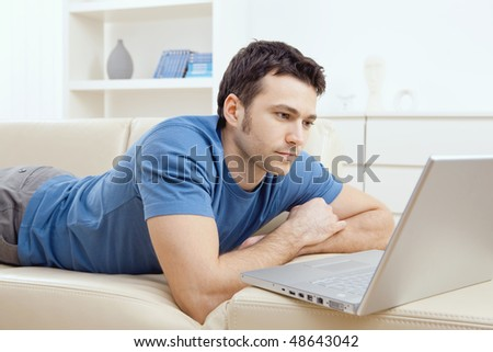 Young man laying on sofa and using laptop at home. - stock photo