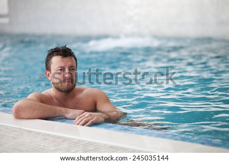 Young man leaning at edge of swimming pool  - stock photo