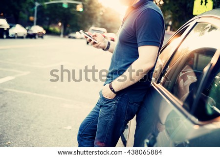 Young man leaning on his car, using a smart phone, Dressed casually. Flare light and vintage post processed. Urban life style, technology, shopping, roadside assistance and job hunting concept. - stock photo