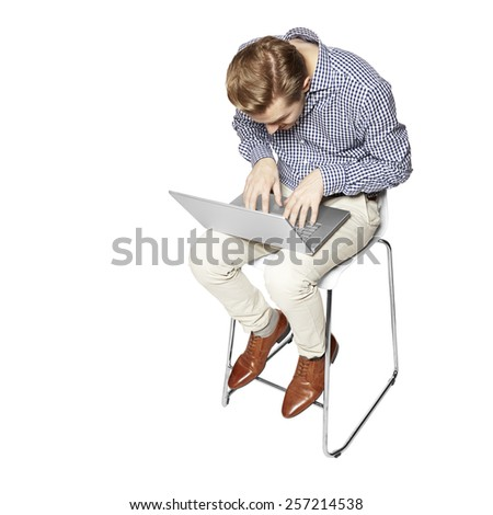 Young man leaning over the keyboard. Isolated on white background. - stock photo