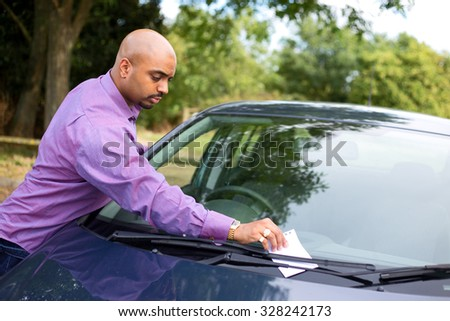 young man leaving a message on a car windscreen