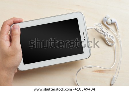 Young man left hand holding small tablet pc screen on wood table with in ear headset beside