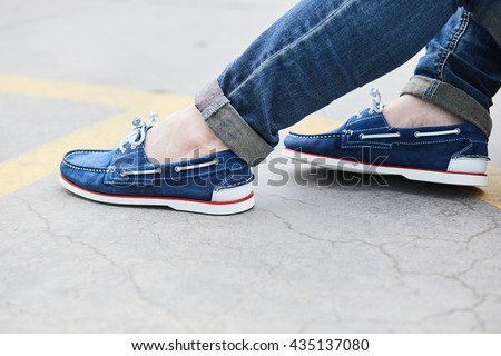 Young man legs on the sidewalk wearing moccasins and jeans, street style - stock photo
