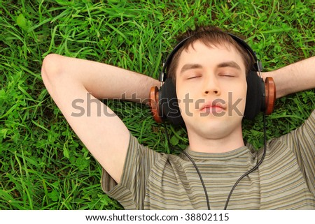 young man lies on grass in headphones - stock photo