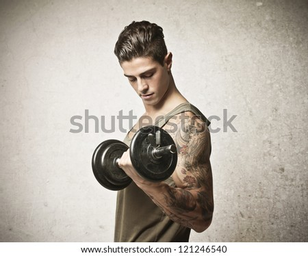 Young man lifting a dumbbell with his left arm, which has a tattoo - stock photo