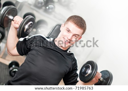 Young man lifting dumbbells in sport club. White background - stock photo