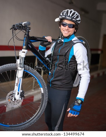 Young Man Lifting His Bicycle; Outdoors - stock photo