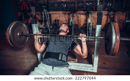 Young man lifting the barbell in the gym. - stock photo