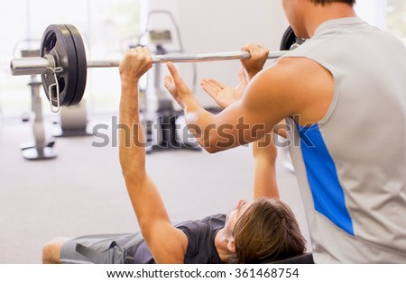 Young man lifting the barbell in the gym