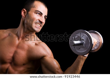 Young man lifting weights against black background - stock photo