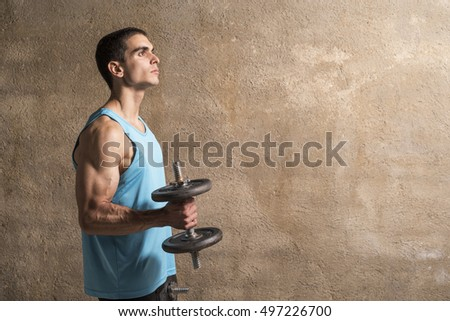 Young man lifting weights in studio shot with wall background