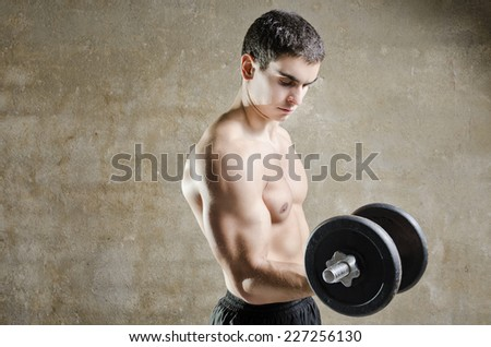 Young man lifting weights training biceps muscle with dumbbells - stock photo