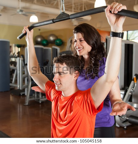 Young Man Lifting Weights with Personal Trainer - stock photo