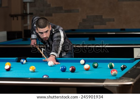 Young Man Lining To Hit Ball On Pool Table - stock photo
