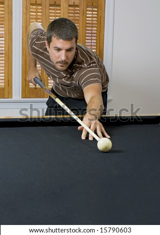 Young man lining up the cue ball, getting ready to break the billiards on the other end of the table. - stock photo