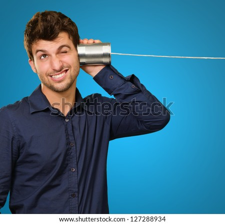 Young Man Listening From Tin Can Phone On Blue Background - stock photo