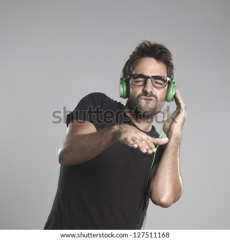 Young man listening music. Boy with headphones on a grey background - stock photo