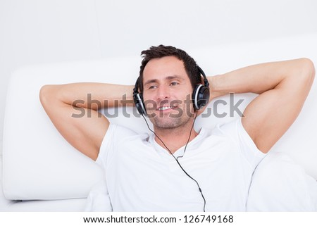 Young Man Listening Music On Headphone, Indoors - stock photo