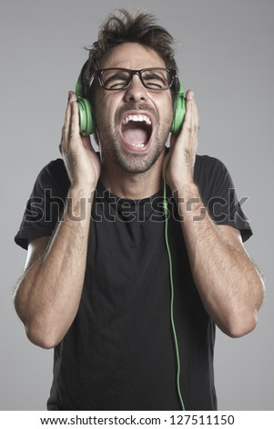 Young man listening music. Squealing boy with headphones