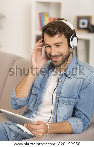 young man listening music with digital tablet at home