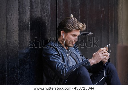 Young man listening music with smartphone earphones sitting in the street black door - stock photo