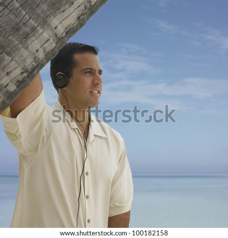 Young man listening to headphones on the beach - stock photo