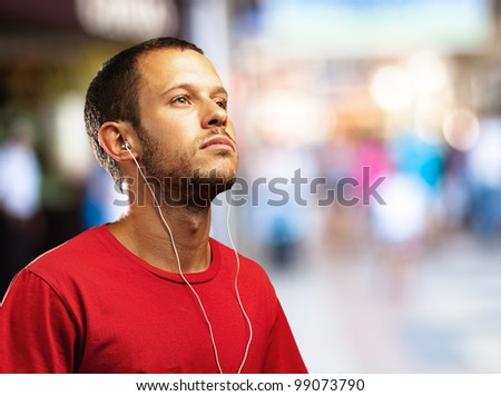 young man listening to music against a city background - stock photo