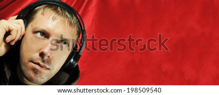 Young man listening to music in headphones against red silky background (copyspace available)