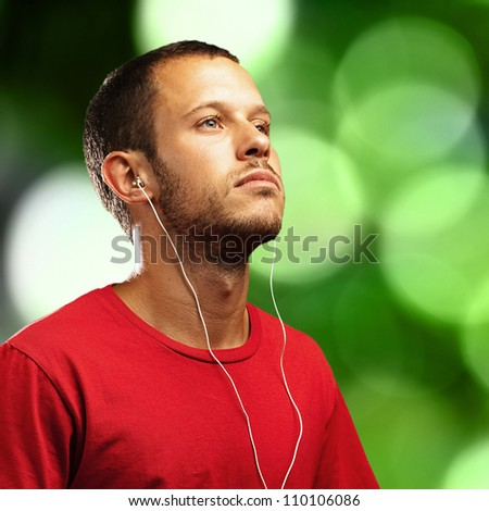 young man listening to music on a green lights background