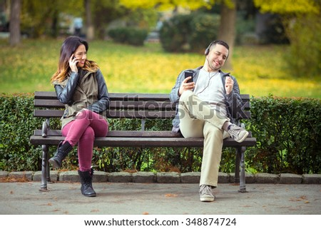Young man listening to music on his smart phone and singing while woman sitting on the same park bench trying to talk on her phone  - stock photo