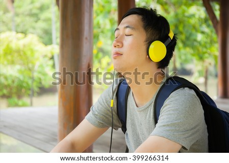Young man listening to music with headphone and carrying a bag in green outdoor park  - stock photo